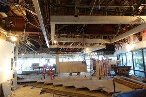 large room under construction with drywall bulkheads framing areas of raised ceilings.